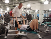 Master trainer, Chris Lutz, assisting in a bench press exercise.